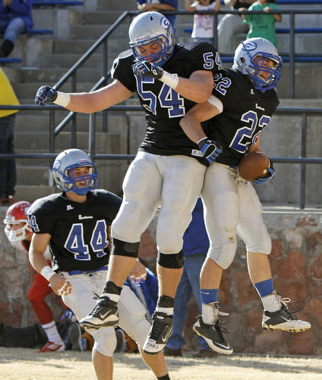 Guthrie's Luke Davis, at right, celebrates with Blake Belcher, center, as John Clark watches after Davis scored a touchdown against Durant in the first round of the Class 5A high school football playoffs in Guthrie, Okla., Saturday, Nov. 12, 2011. Photo by Bryan Terry, The Oklahoman