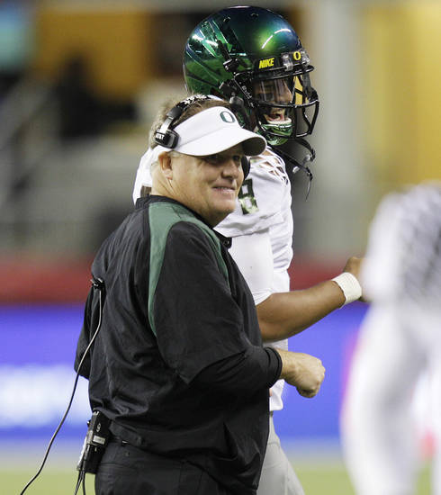   Oregon head coach Chip Kelly, left, talks with quarterback Marcus Mariota late in the second half of an NCAA college football game against Washington State, Saturday, Sept. 29, 2012, in Seattle. Oregon beat Washington State 51-26. (AP Photo/Ted S. Warren)  
