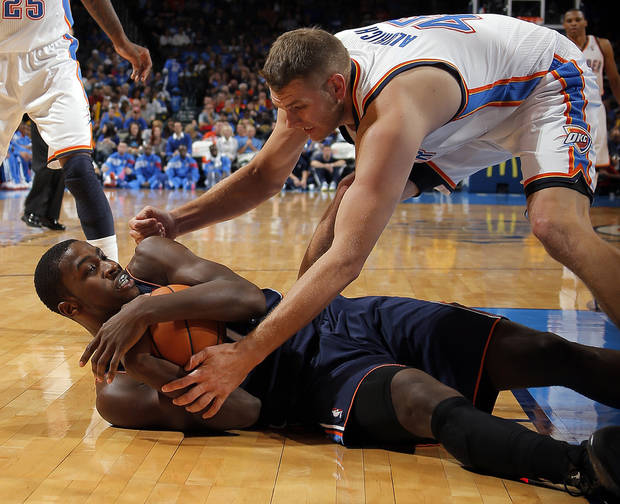 Oklahoma City's Cole Aldrich (45) wrestles Charlotte's Michael Kidd-Gilchrist (14) for a loose ball during the preseason NBA game between the Oklahoma City Thunder and the Charlotte Bobcats at Chesapeake Energy Arena in Oklahoma City, Tuesday, Oct. 16, 2012. Photo by Sarah Phipps, The Oklahoman