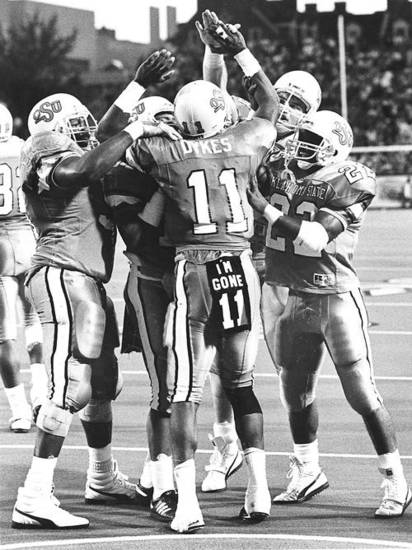 OSU COLLEGE FOOTBALL: Hart Lee Dykes is congratulated by teammates after a touchdown in 1988 against Texas A&M.