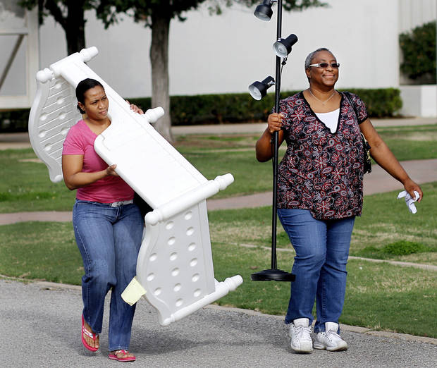 "Shaketta Khalid carries a toddler's bed frame and her friend, Josie Ford, carries a floor lamp as the two leave  a giant ""garage sale""   at State Fair Park Saturday, March 31, 2012.   Ford said she came hoping to find  a lamp and she was delighted when she found  this one.    Photo by Jim Beckel, The Oklahoman"
