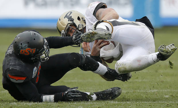 Oklahoma State's Daytawion Lowe (8) brings down Purdue's Robert Marve (9) during the Heart of Dallas Bowl football game between Oklahoma State University and Purdue University at the Cotton Bowl in Dallas, Tuesday, Jan. 1, 2013. Oklahoma State won 58-14. Photo by Bryan Terry, The Oklahoman