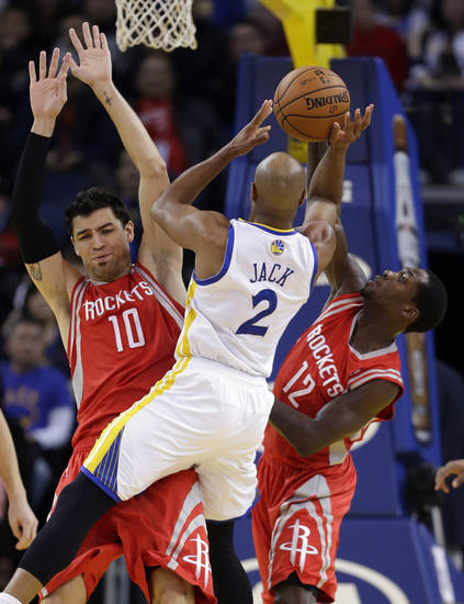 Golden State Warriors' Jarrett Jack (2) tries to shoot in front of Houston Rockets' Carlos Delfino (10) and Patrick Beverley (12) during the first half of an NBA basketball game in Oakland, Calif., Tuesday, Feb. 12, 2013. (AP Photo/Marcio Jose Sanchez)