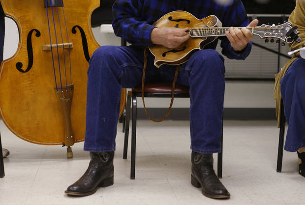 Ron Reser, of Shawnee, plays during a bluegrass jam session.