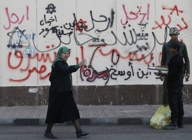 "A woman walks past Arabic writings on a wall that read, ""no, leave, Muslim Brotherhood,"" in front of the presidential palace in Cairo, Egypt, Thursday, Dec. 13, 2012. Egypt's opposition called on its followers to vote ""no"" in a crucial referendum on a disputed constitution drafted by Islamist supporters of President Mohammed Morsi. (AP Photo/Hassan Ammar)"