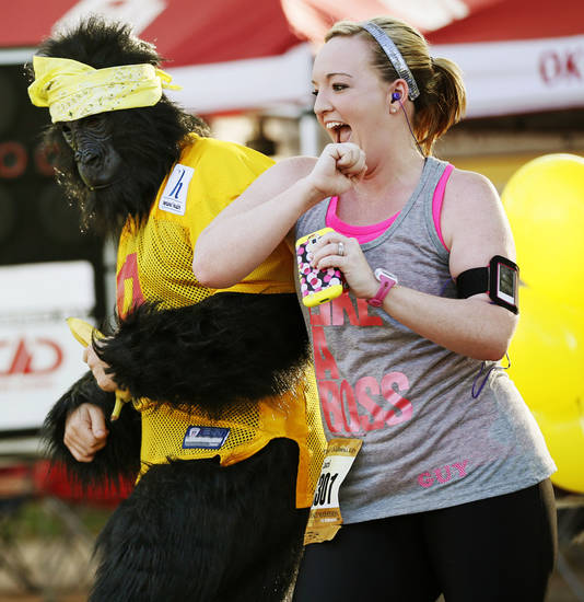 Runner Laci Dilibero takes a break from her race to dance with Reed Hammond in a gorilla costume on Gorilla Hill near NW 40th and Shartel Ave. during the Oklahoma City Memorial Marathon in Oklahoma City, Sunday, April 28, 2013. Photo by Nate Billings, The Oklahoman