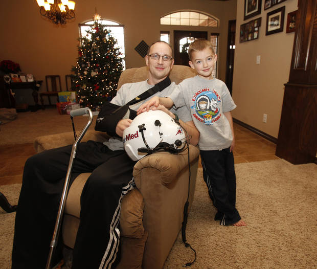 Michael Eccard and his son, Josh, 5, are in their Edmond home. Eccard is the sole survivor of a medical helicopter flight crash in July. PHOTO BY JIM BECKEL, THE OKLAHOMAN
