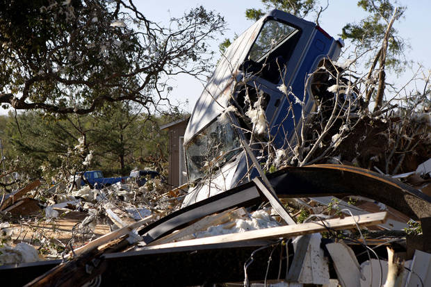 An vehicle sits in a tree in Tushka, Okla., Friday, April 15, 2011, following a tornado the night before. (AP Photo/Sue Ogrocki)