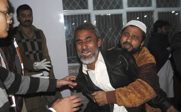 Pakistanis mourn for their relative killed in a suicide bombing, at a local hospital in Peshawar, Pakistan, Saturday, Dec. 22, 2012. A suicide bomber in Pakistan killed several people including a provincial government official at a political rally held Saturday by a party that has opposed the Taliban, officials said. (AP Photo/Mohammad Sajjad)