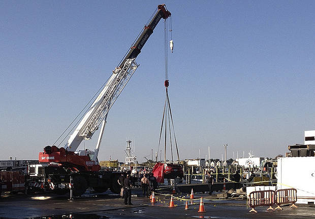 A crane lifts a car from the water in Newport, R.I., Friday, Oct. 5, 2012. The U.S. Coast Guard said three people were found inside the car, which was submerged for hours in the Newport shipyard. (AP Photo/Newport Daily News, Matt Sheley)