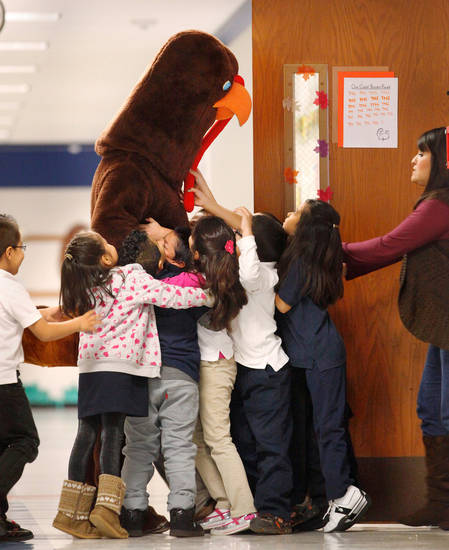 Children cheered and laughed and rushed to touch this 7 foot-tall turkey as he walked through the halls of Herronville Elementary School at SW 29 and McKinley Tuesday morning, Nov. 22, 2011. Inside the turkey suit was Leon Hill, a veteran educator who is serving his first year as principal at this south Oklahoma City Public School. Last month, Hill issued a reading challenge to his students, which range from pre-kindergarten through fifth grade.  He promised that if they would read at least 3,000 books, he would come to school dressed as a turkey before the Thanksgiving break. The students accepted the challenge and exceeded their goal,  reading a total of 4,444 books.   Hill credited the success of the reading challenge to the school's teachers and to the parents who either read with their children or encouraged them  to read.    Photo by Jim Beckel, The Oklahoman