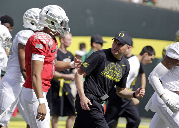 FILE - In this April 7, 2013, file photo, Oregon coach Mark Helfrich, right, looks back at quarterback Marcus Mariota as they run onto the field for their spring NCAA college football game in Eugene, Ore. The NCAA's Division I Committee on Infractions will release a public report on the findings of its investigation and any possible sanctions against Oregon's football program on Wednesday morning, June 26, 2013.  (AP Photo/Don Ryan, File) ORG XMIT: NY169