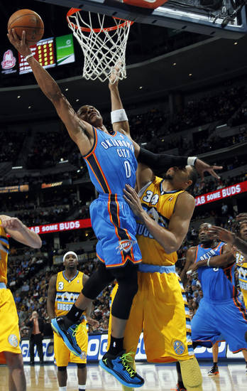 Oklahoma City Thunder guard Russell Westbrok, left, goes up for a shot past Denver Nuggets forward JaVale McGee in the first quarter of an NBA basketball game in Denver on Sunday, Jan. 20, 2013. (AP Photo/David Zalubowski)