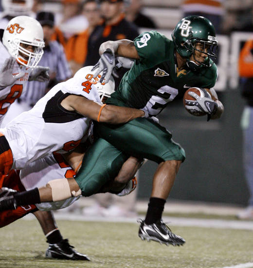 Brandon Whitaker, Edmond Santa Fe graduate, tries to break the tackle of Patrick Lavine during the second half of the  college football game between Oklahoma State University and Baylor University at Floyd Casey Stadium in Waco, Texas, Saturday, Nov. 17, 2007. BY STEVE SISNEY, THE OKLAHOMAN