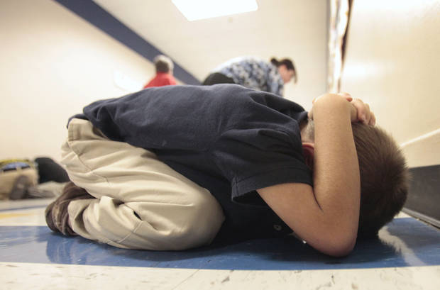 Heronville Elementary School first-grader Jesse Rice covers his head during a tornado drill this week. Photos by DAVID McDANIEL, THE OKLAHOMAN