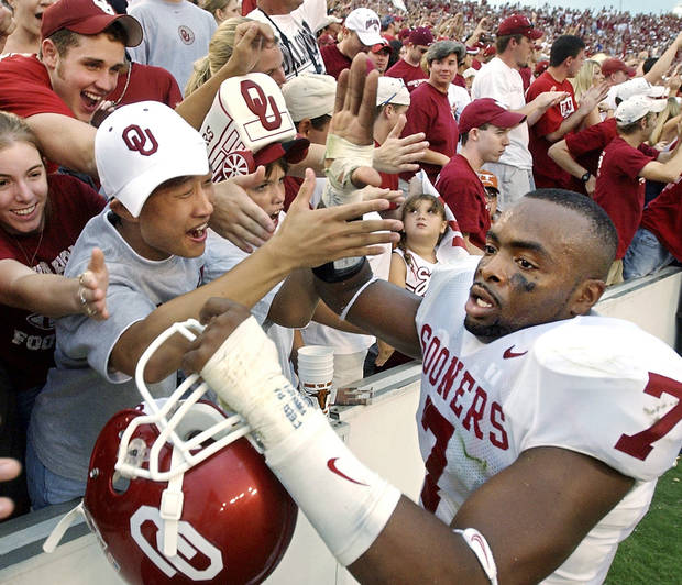 DALLAS, 10/11/2003: Jubilant OU fans congratulate players who pass in front of the stands while celebrating their 65-13 win over Texas in the Cotton Bowl.  (7) is Brandon Everage.    Staff photo by Jim Beckel.