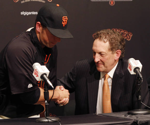 San Francisco Giants' Buster Posey, left, shakes hands with Giants president Larry Baer after a news conference, Friday, March 29, 2013 in San Francisco. The Giants and Posey have reached an agreement on a new nine year contract through 2021 with an option for the 2022 season. (AP Photo/George Nikitin)
