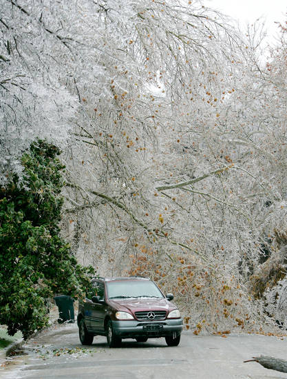 WINTER / COLD / WEATHER / ICE STORM / SPORT UTILITY VEHICLE: An SUV drives under ice-covered trees near NW 14th and Harvey in Heritage Hills in Oklahoma City , Okla. Dec. 10, 2007.  BY STEVE GOOCH, THE OKLAHOMA.   ORG XMIT: KOD
