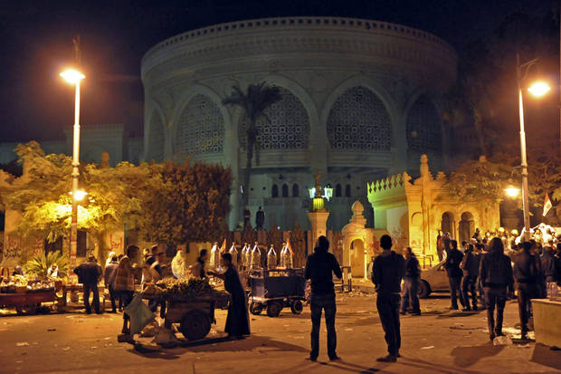 Vendors provide demonstrators with food and drink outside the presidential palace, after tens of thousands marched on the presidential palace pushing past barbed wire fences installed by the army, in Cairo, Egypt. during the early hours of Saturday, Dec. 8, 2012. Egypt postponed early voting on a contentious draft constitution, and aides to President Mohammed Morsi floated the possibility of canceling the whole referendum in the first signs Friday that the Islamic leader is finally yielding to days of protests and deadly street clashes. (AP Photo/Hussein Tallal)