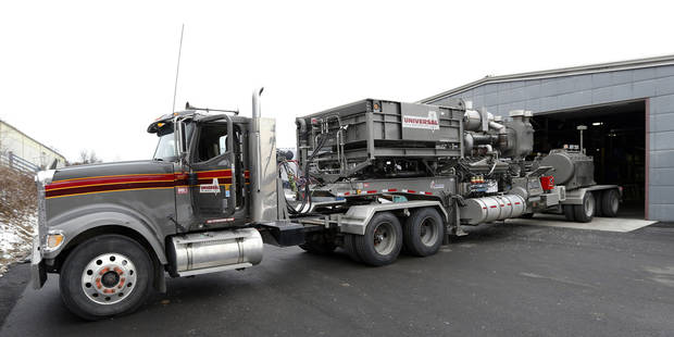In this photo made on Thursday, Jan. 17, 2013, the truck and trailer rig with a huge converted engine that runs a pump used in extracting gas from wells, sets outside the Cummins Bridgeway facility in Gibsonia, Pa. The unit on the front of the trailer cools the 50 litre, 16 cylinder Cummins diesel engine that occupies the center of the trailer. The pump for the fracking fluid is at the rear. Oil- and gas-field companies from Pennsylvania to Texas are experimenting with converting the huge diesel engines that operate pumps that propel millions of gallons of water, sand and chemicals down a well bore in the fracturing process to break apart rock or tight sands that trap natural gas. (AP Photo/Keith Srakocic)