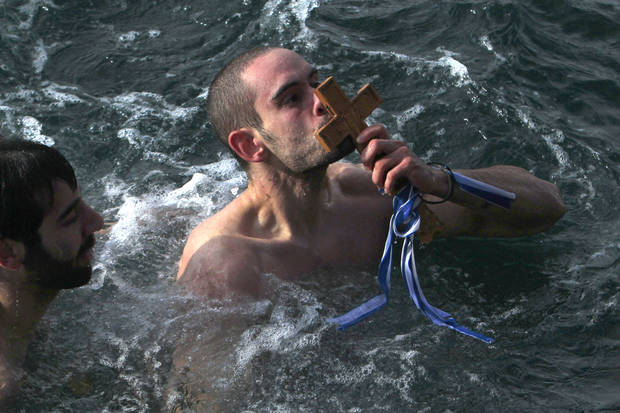 Giorgos Ypsilantis, kisses the wooden cross after being the first to retrieve it, during an Epiphany ceremony to bless the water in Greece's northern port city of Thessaloniki, on Sunday, Jan. 6, 2013. The traditional ceremony marks the Epithany, and similar ceremonies are held across Greece on river banks, seafronts and lakes, when an Orthodox priest throws a simple wooden cross into the water and swimmers race to be the first to retrieve it. (AP Photo/Nikolas Giakoumidis)