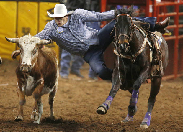 Jutin Thigpen of Waycross, Ga., leaps for a steer during the steer wrestling in the International Finals Rodeo inside the State Fair Arena in Oklahoma City, Friday, Jan. 18, 2013. Photo by Bryan Terry, The Oklahoman
