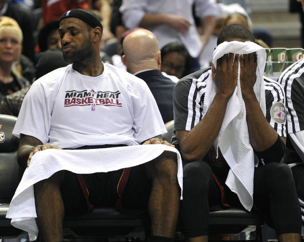 Miami Heat's LeBron James, left , and Dwyane Wade sit on the bench in the closing seconds of an NBA basketball game against the Milwaukee Bucks, Saturday, Dec. 29, 2012, in Milwaukee.  The Bucks defeated the Heat 104-85. (AP Photo/Jim Prisching)