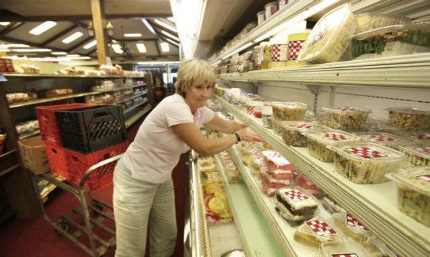 Terry Sinclair, owner of Soup Soups,  stocks the shelves at the Crescent Market in Nichols Hills. <strong>Steve Gooch</strong>