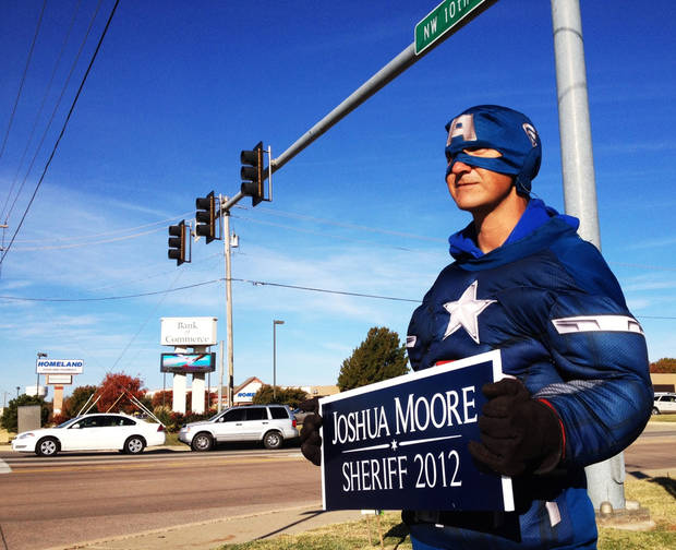 Tommy Reyes holds a campaign sign for Joshua Moore at NW 10th and Czech Hall Road in Yukon.
