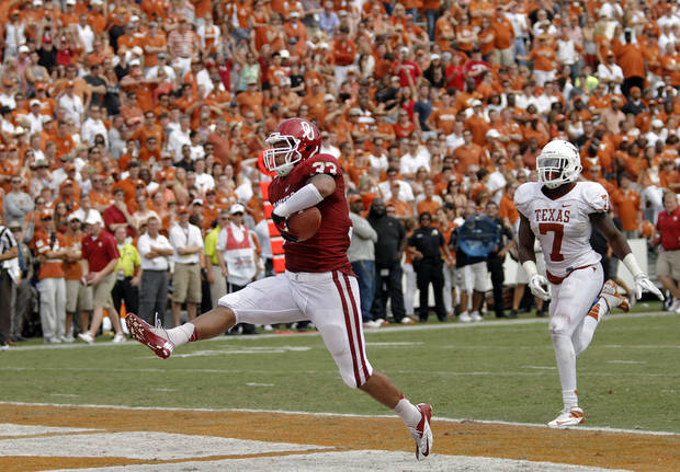 OU&#039;s Trey Millard (33) high steps in the end zone for a touchdown past UT&#039;s Demarco Cobbs (7) during the Red River Rivalry college football game between the University of Oklahoma (OU) and the University of Texas (UT) at the Cotton Bowl in Dallas, Saturday, Oct. 13, 2012. Photo by Chris Landsberger, The Oklahoman