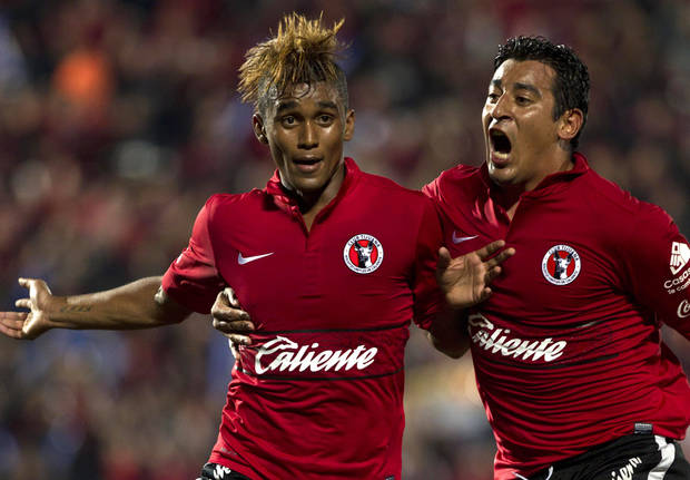 Tijuana's Fidel Martinez, left, celebrates after scoring with his teammate Alfredo Moreno during a Mexican soccer league match in Tijuana, Mexico, Thursday, Nov. 29, 2012. (AP Photo/Christian Palma)