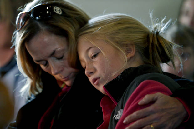 Molly Delaney, left, holds her 11-year-old daughter, Milly Delaney, during a service in honor of the victims who died a day earlier when a gunman opened fire at Sandy Hook Elementary School in Newtown, Conn., as people gathered at St. John's Episcopal Church , Saturday, Dec. 15, 2012, in the Sandy Hook village of Newtown, Conn. The massacre of 26 children and adults at Sandy Hook Elementary school elicited horror and soul-searching around the world even as it raised more basic questions about why the gunman, 20-year-old Adam Lanza, would have been driven to such a crime and how he chose his victims.  (AP Photo/Julio Cortez) ORG XMIT: CTJC116