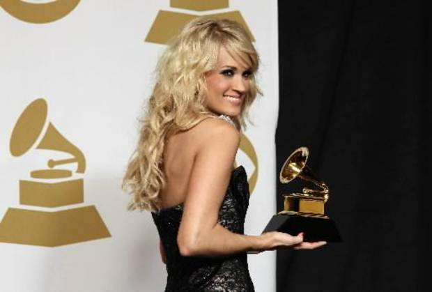 """Carrie Underwood poses backstage with the award for best country solo performance for """"Blown Away"""" at the 55th annual Grammy Awards on Sunday, Feb. 10, 2013, in Los Angeles. (AP)"""