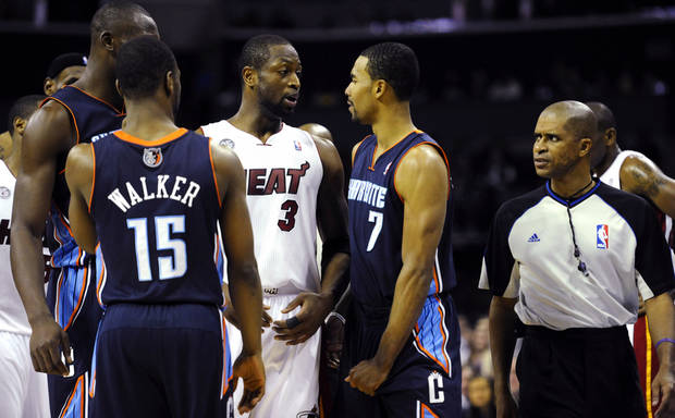 Miami Heat&#039;s Dwyane Wade (3) and Charlotte Bobcats&#039; Ramon Sessions (7) interact after Sessions was called for a foul as referee Zach Zarba (33) watches during the second half of their NBA basketball game, Wednesday, Dec. 26, 2012, in Charlotte. The Heat won 105-92. (AP Photo/The Charlotte Observer, David T. Foster III) MAGS OUT; TV OUT; NEWSPAPER INTERNET ONLY