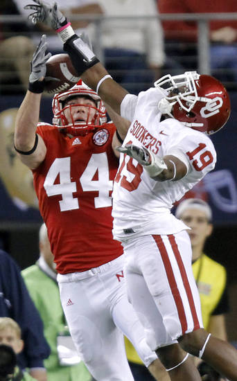 Oklahoma's Demontre Hurst (19) breaks up a pass for Nebraska's Mike McNeill (44) during the Big 12 football championship game between the University of Oklahoma Sooners (OU) and the University of Nebraska Cornhuskers (NU) at Cowboys Stadium on Saturday, Dec. 4, 2010, in Arlington, Texas.  Photo by Chris Landsberger, The Oklahoman