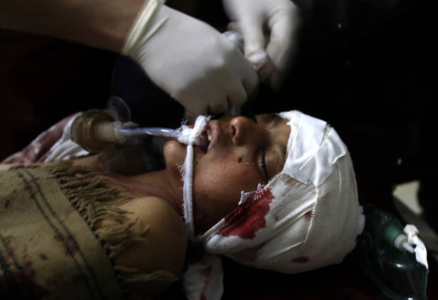 A doctor treats a Pakistani boy who was injured in a suicide bombing, at a local hospital in Peshawar, Pakistan, Friday, Feb. 1, 2013. A suicide bomber detonated his explosives outside a Shiite mosque in northwestern Pakistan as worshippers were leaving Friday prayers, killing several people and wounding dozens in the latest apparent sectarian attack in the country, police said.(AP Photo/Mohammad Sajjad)