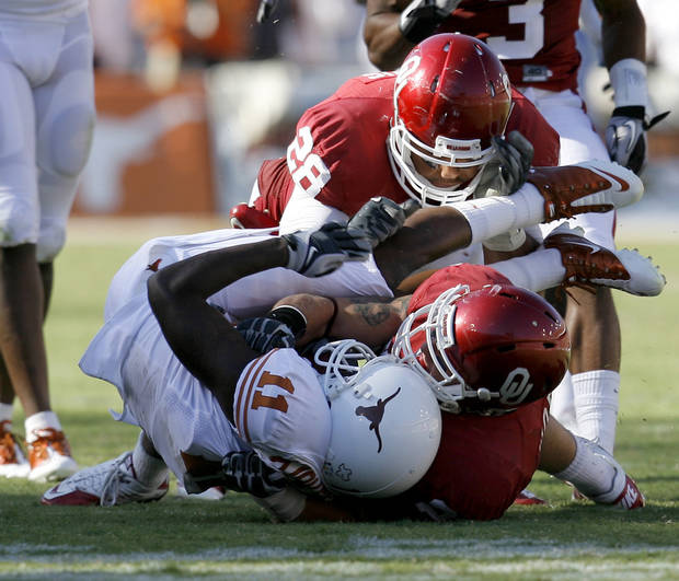 OU's Travis Lewis, top, and Tom Wort bring down James Kirkendoll of Texas during the second half of the Red River Rivalry college football game between the University of Oklahoma Sooners (OU) and the University of Texas Longhorns (UT) at the Cotton Bowl on Saturday, Oct. 2, 2010, in Dallas, Texas. OU defeated Texas 28-20.    Photo by Bryan Terry, The Oklahoman