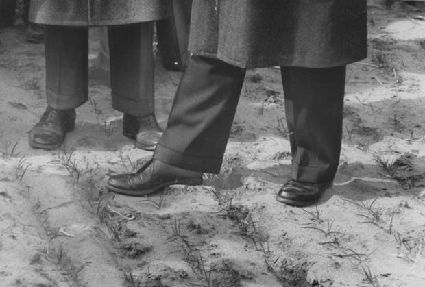 U.S. President Dwight D. Eisenhower's shoes (foreground) and those of Secretary Benson's stir dust in Carl Peoples' sparse wheat field near Woodward during a 1957 visit to Oklahoma. STAFF PHOTO BY RICHARD COBB, THE OKLAHOMAN