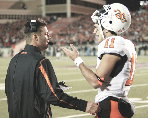 Mike Gundy talks with Zac Robinson during Saturday's loss. PHOTO By Steve Sisney, The Oklahoman