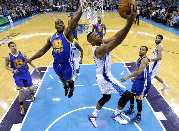 New Orleans Hornets guard Eric Gordon scores next to Golden State Warriors forward Carl Landry (7) during the first half of an NBA basketball game in New Orleans, Saturday, Jan. 19, 2013. (AP Photo/Jonathan Bachman)