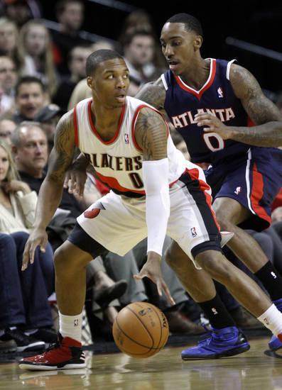 Atlanta Hawks guard Jeff Teague, right, plays tight defense on Portland Trail Blazers guard Damian Lillard during the first half of their NBA basketball game in Portland, Ore., Monday, Nov. 12, 2012. (AP Photo/Don Ryan)