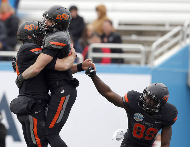 Oklahoma State&#039;s J.W. Walsh (4), Blake Webb (85) and Nick Rockwell (89) celebrate a touchdown during the Heart of Dallas Bowl football game between the Oklahoma State University (OSU) and Purdue University at the Cotton Bowl in Dallas,  Tuesday,Jan. 1, 2013. Photo by Sarah Phipps, The Oklahoman
