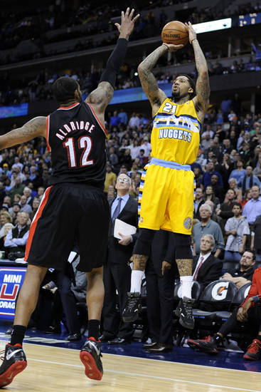 Denver Nuggets guard Wilson Chandler (21) shoots a 3-pointer against Portland Trail Blazers forward LaMarcus Aldridge (12) in the final minute of overtime of an NBA basketball game, Tuesday, Jan. 15, 2013, in Denver. Denver won 115-111. (AP Photo/Jack Dempsey)