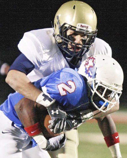 Kingfisher's Jordan Woods, top, brings down Millwood's Emilio Gatewood during Saturday's game. Photo by Chris Landsberger, The Oklahoman