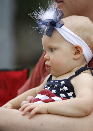 One year old Avery Martin enjoys the LibertyFest Parade in downtown Edmond, OK, from the arms of her father Steven, Saturday, July 4, 2009. By Paul Hellstern, The Oklahoman