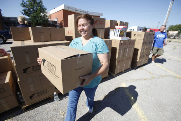 Volunteer Terri Roberts takes a box to a waiting car during a joint food drive with Feed The Children and Mustard Seed Development Corporation.