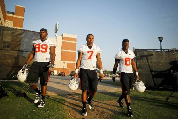 Defensive players Nigel Nicholas (89), Shamiel Gary (7), and Daytawion Lowe (8) walk onto the field before OSU's first practice of the season on the campus of Oklahoma State University in Stillwater, Okla. on Friday, August 5, 2011. Photo by Zach Gray