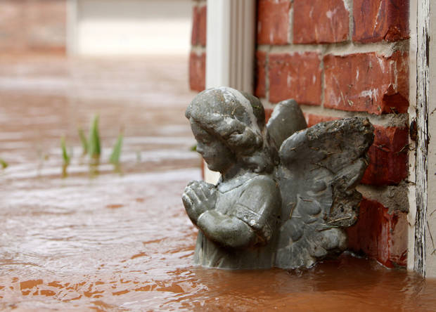 An angel statue is up to her waist in floodwaters next to this house in the Palo Verde Addition in Edmond, OK. Flood waters inundated a number of homes in the area after record rainfall, Monday, June 14, 2010. By Paul Hellstern, The Oklahoman