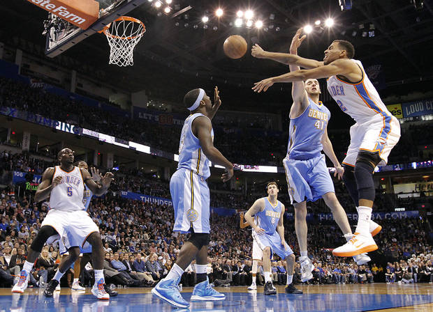 Oklahoma City's Thabo Sefolosha (2) passes the ball past Denver's Ty Lawson (3) and Kosta Koufos (41) during the NBA basketball game between the Oklahoma City Thunder and the Denver Nuggets at the Chesapeake Energy Arena on Wednesday, Jan. 16, 2013, in Oklahoma City, Okla.  Photo by Chris Landsberger, The Oklahoman