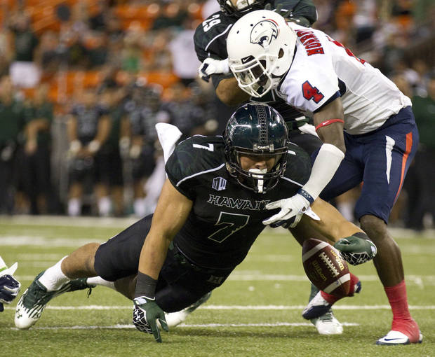 Hawaii running back Joey Iosefa (7) fumbles the football while diving for the endzone as Southern Alabama Darrius Morrow cornerback (4)  tackles Iosefa in the first quarter of an NCAA college football game Saturday, Dec. 1, 2012, in Honolulu. Hawaii recovered the fumble on the play. (AP Photo/Eugene Tanner)